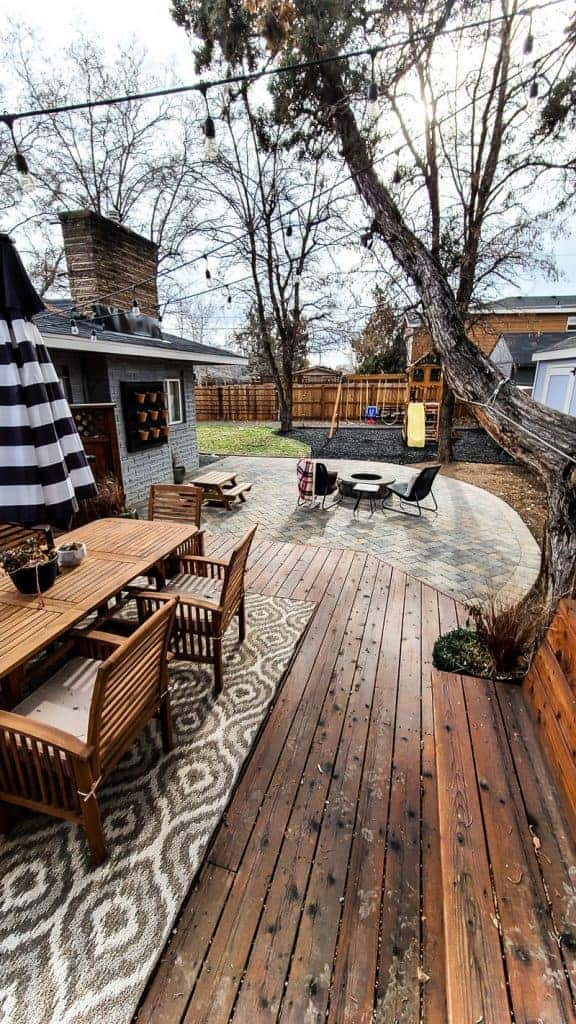 patio space view from the deck showing outdoor dining area on wood deck with large curved paver patio with round fire pit and chairs around it with wooden play set and grass in the background