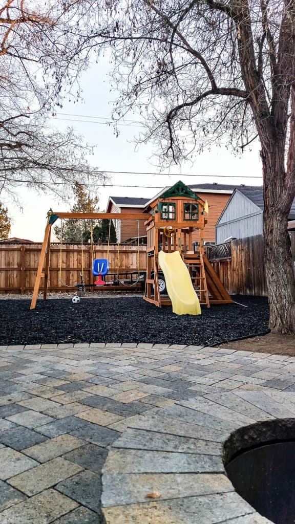 shows a swing set with rubber bark and paver patio in foreground