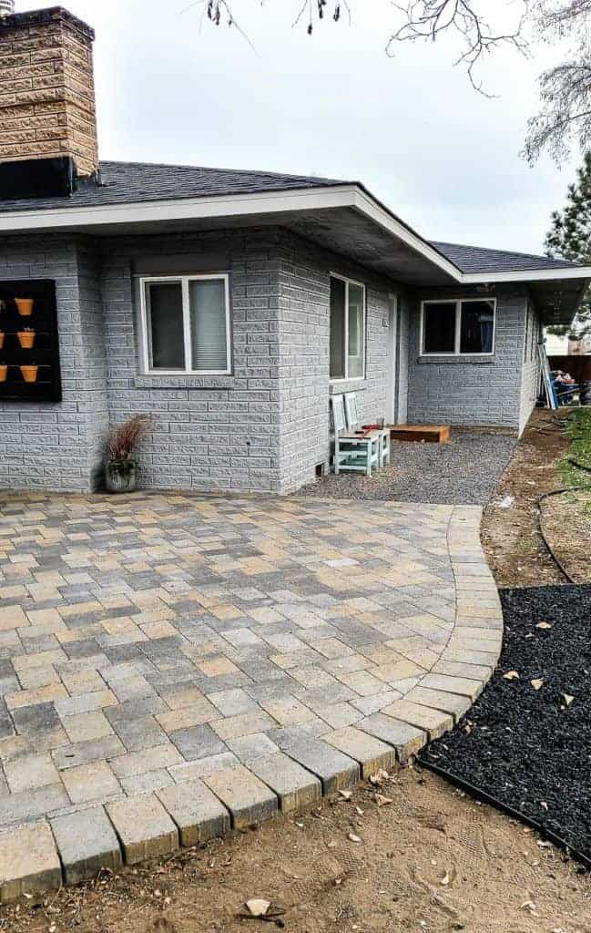 shows paver patio with curved edges and gravel by backdoor