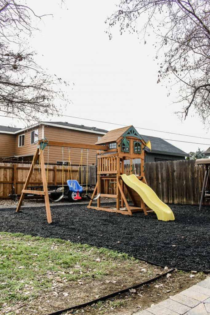 shows a kids swing set with slide and roof and rubber bark base in residential backyard