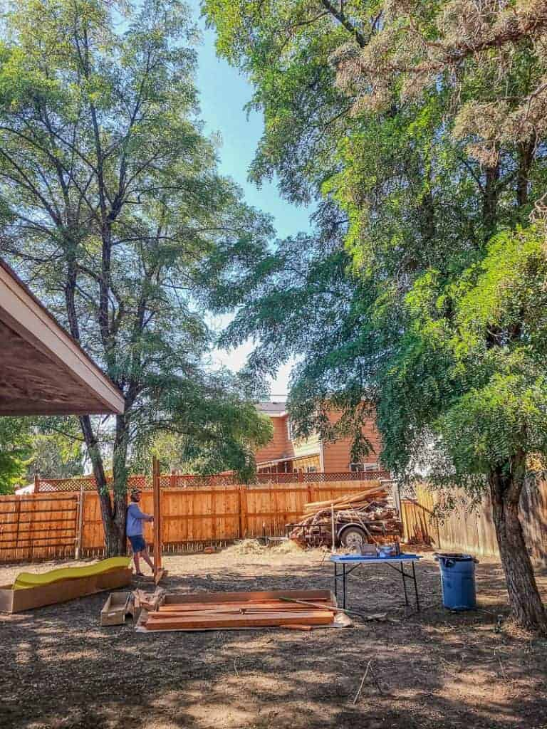 Man setting up new wooden playset in backyard