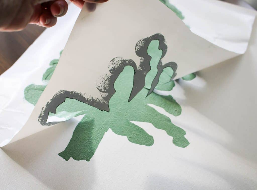 shows a stencil being pulling off the canvas with tree print