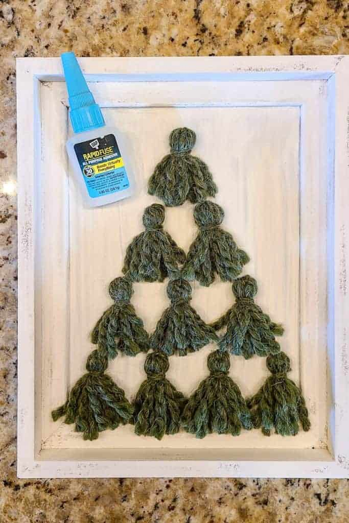 Small green Christmas tree tassels glued to frame with glue