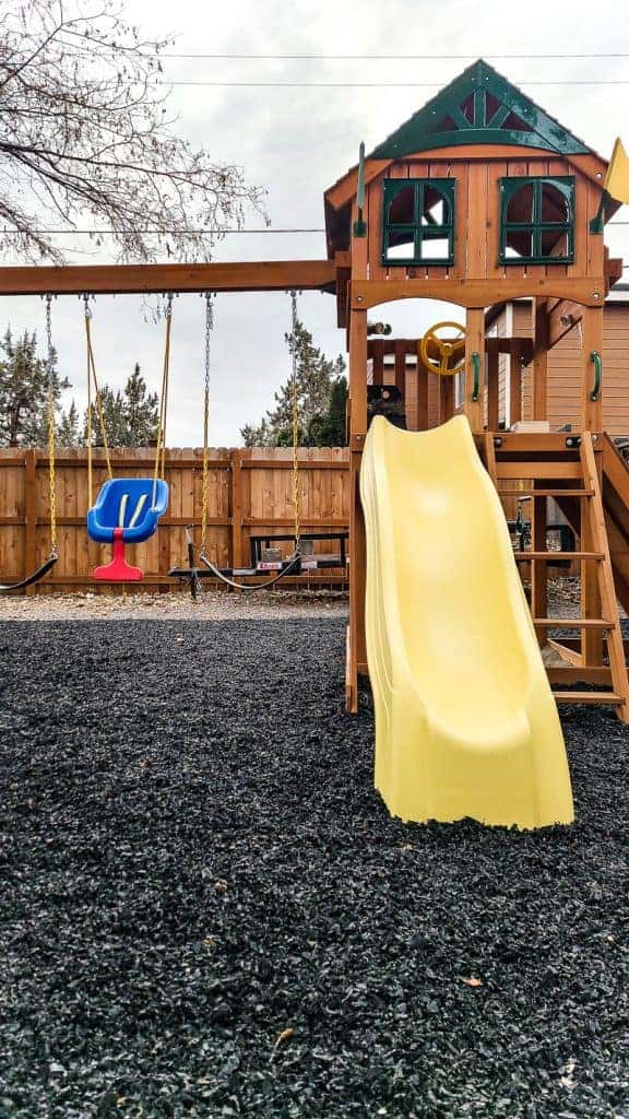 wooden Swing set on black rubber mulch with yellow slide