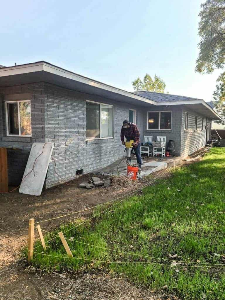 Man using jack hammer to remove concrete pad and ramp by backdoor in backyard during renovation