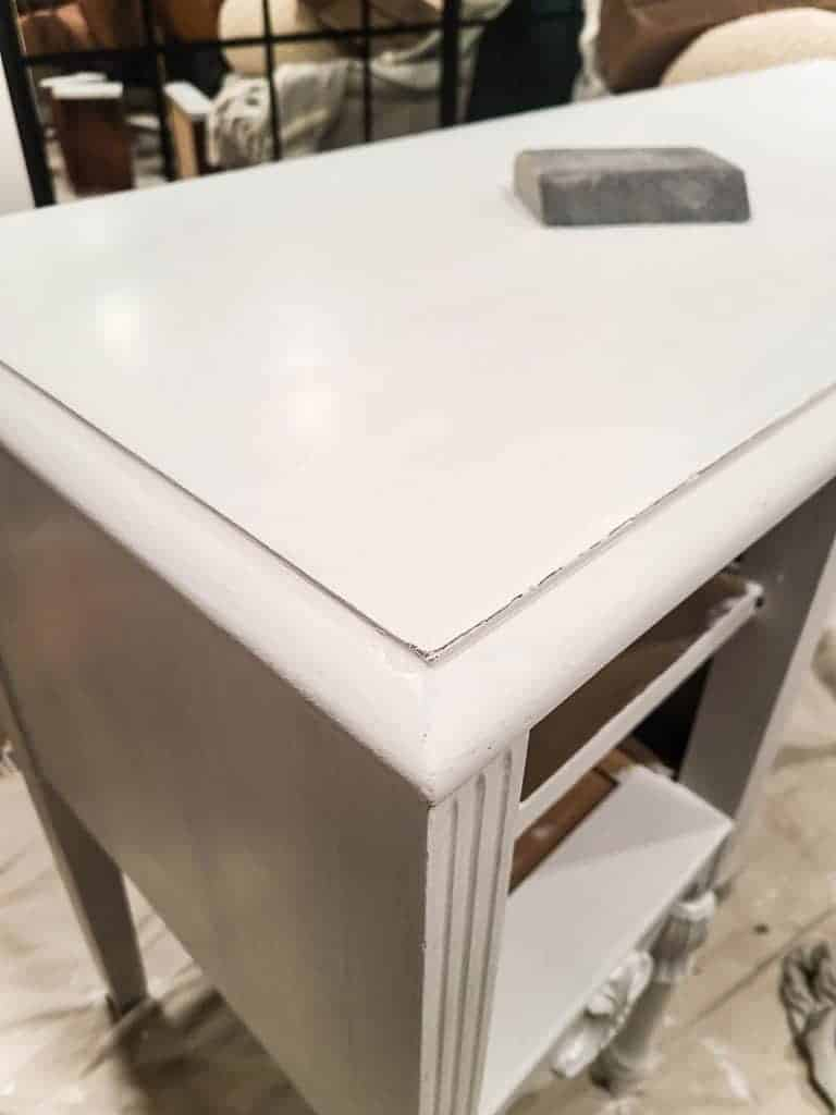 shows a corner of the desk painted with white chalk paint after being slightly distressed with a sanding block