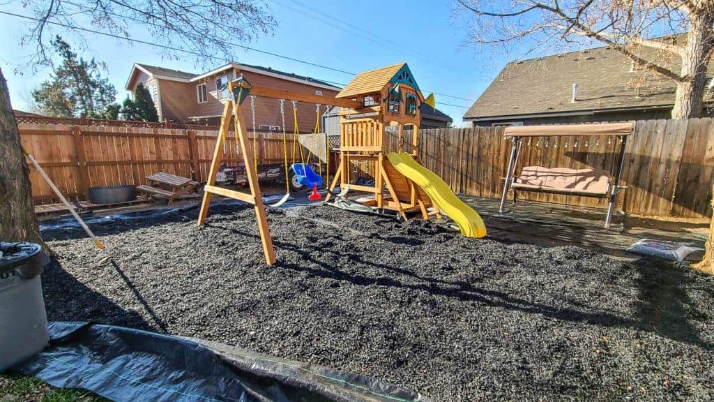 shows a kids swing set with rubber mulch getting spread out