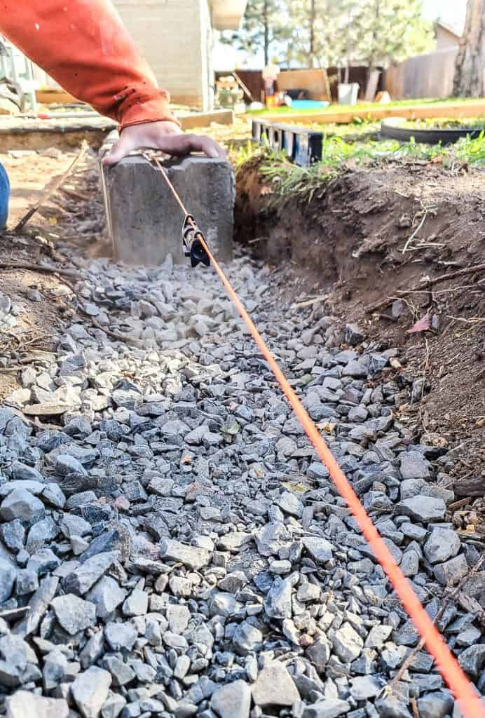someone holds a retaining wall block steady in the gravel trench with a string line and level hanging over it