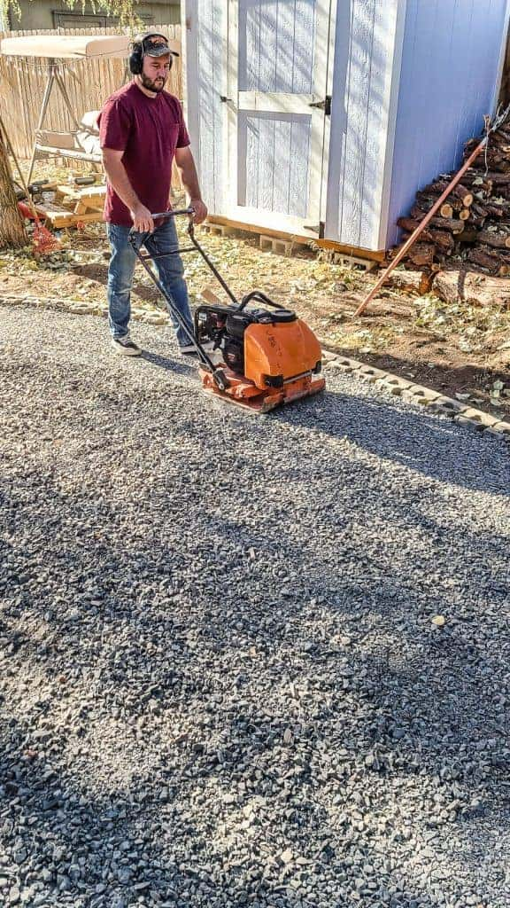 man uses a plate compactor on gravel base before installing a paver patio