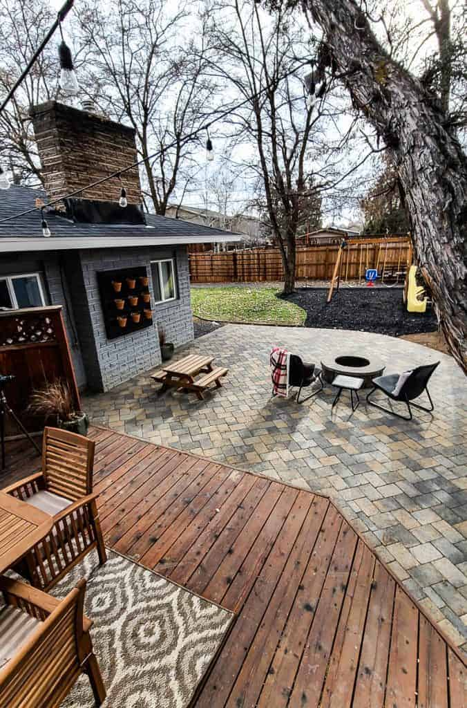 entire view of family friendly renovated backyard for little kids with wooden swing set with rubber ground cover, grass area, wooden fence, paver patio with fire pit for entertaining and wooden deck with plenty of seating for dining outside