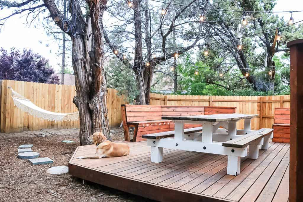 shows new backyard patio with large farmhouse wooden table, string lights overhead hanging from trees, fence in background and macrame hammock