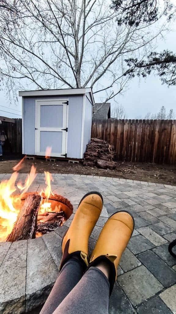 shows a shed in the background of the fireplace and yellow boots propped up on fire pit