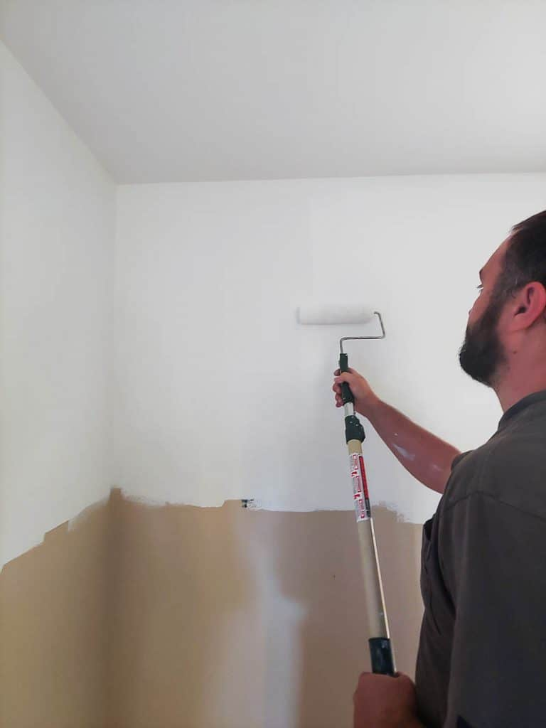 Man rolling white paint onto tan walls with paint roller