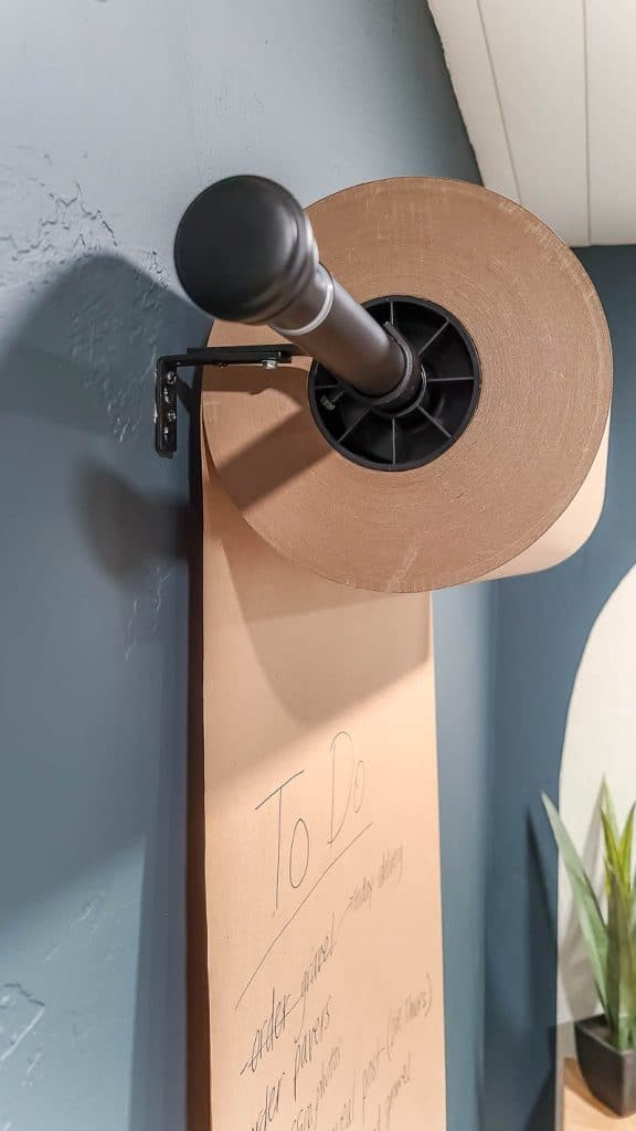 shows the Kraft paper on the dispenser roll hanging on wall in home office with dark green walls