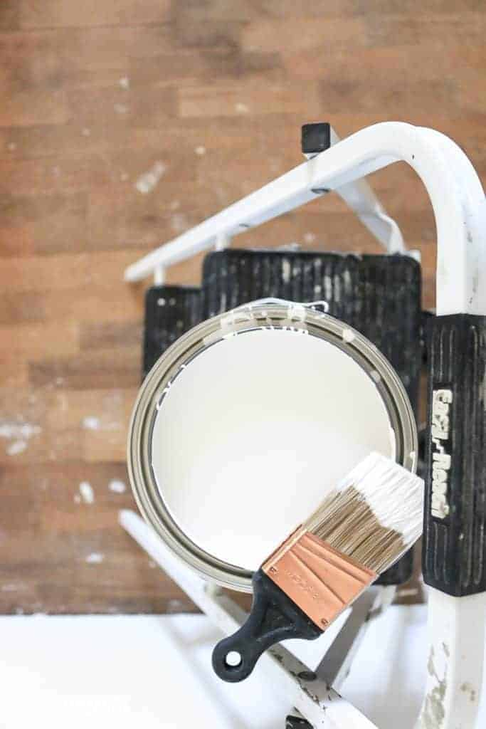 Top down view of can of white paint  on top of a step ladder with angeled paint brush sitting on top of the edge