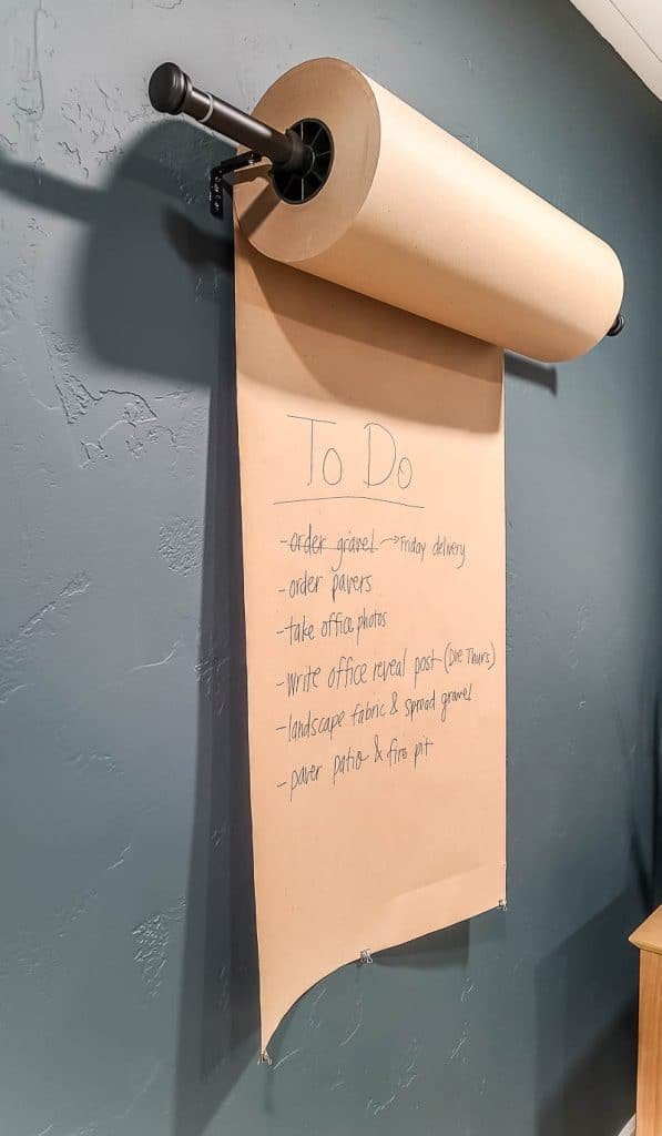 shows wall mounted dispenser roll of Kraft paper in home office with to do list on it