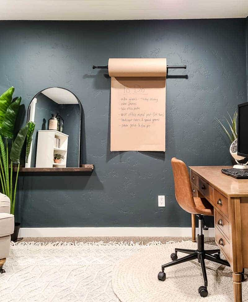 shows the paper wall dispenser on a dark green painted wall with a to do list on it with shelf, mirror, tree and desk in surrounding area