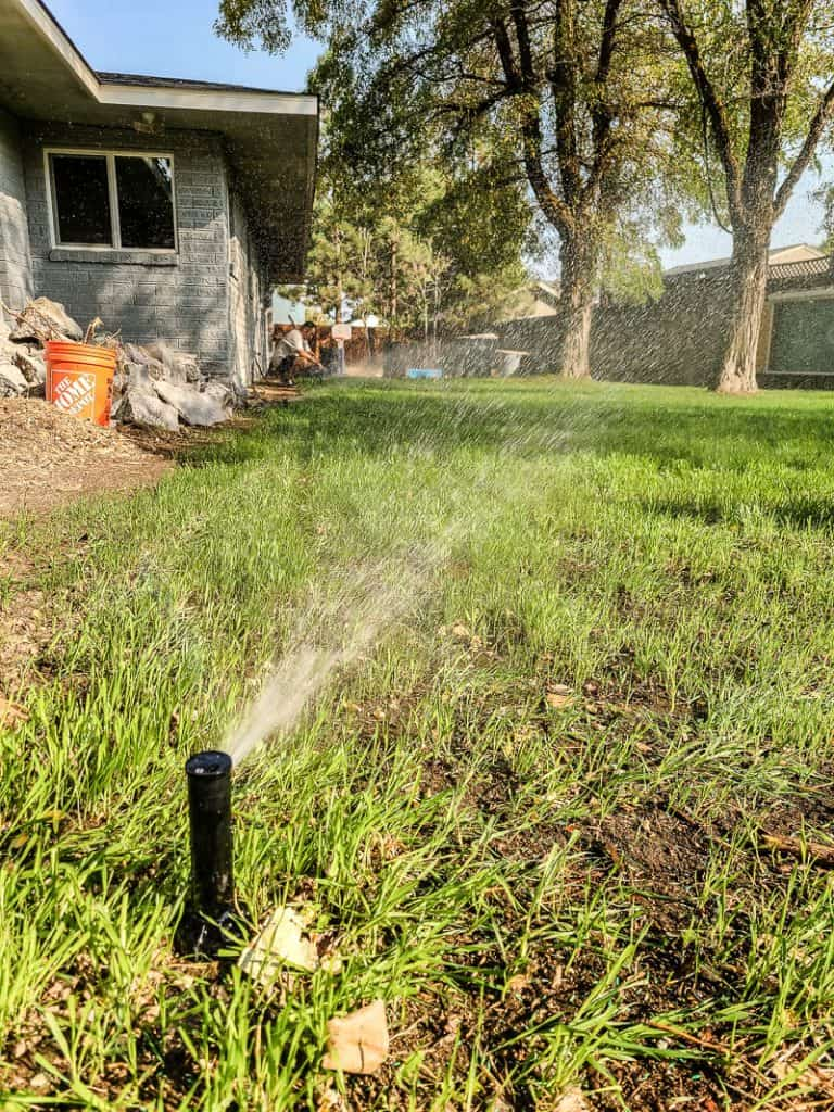 shows a sprinklers watering the lawn in backyard