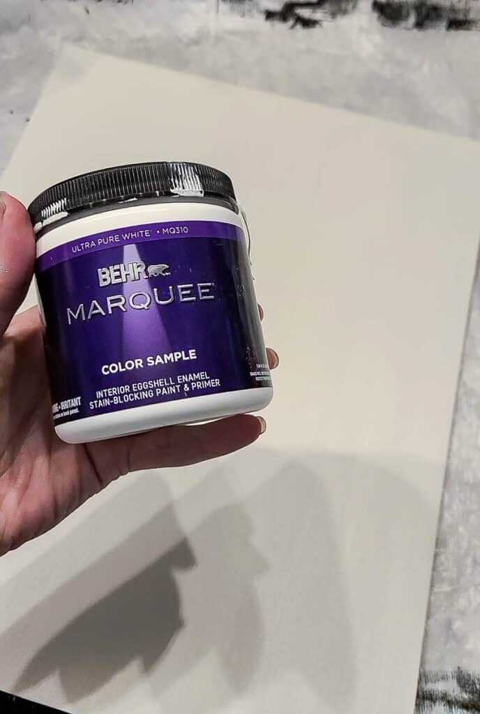 hand holding a Jar of Behr color sample
