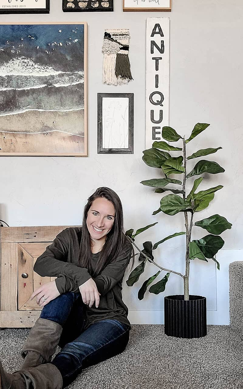 Girl sitting on ground next to faux fiddle leaf fig tree with black fluted planter pot cover on the base