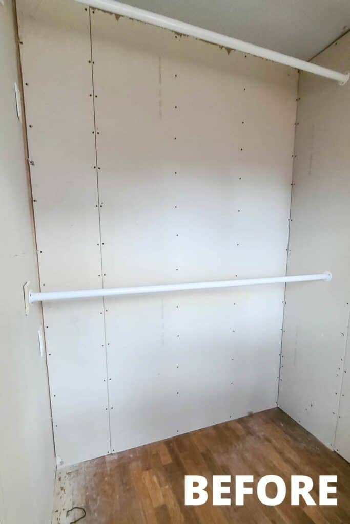 empty small walk in master closet before with unfinished drywall and two closet rods for hanging