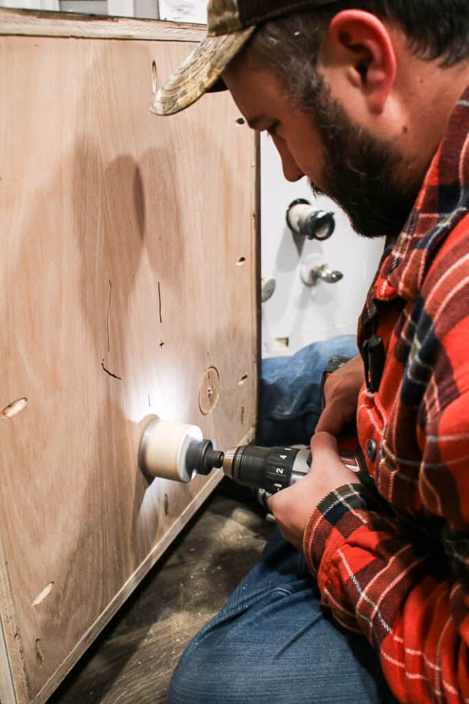 shows a man drilling a hole in the wooden back panel of cabinet with a hole saw for plumbing pipes