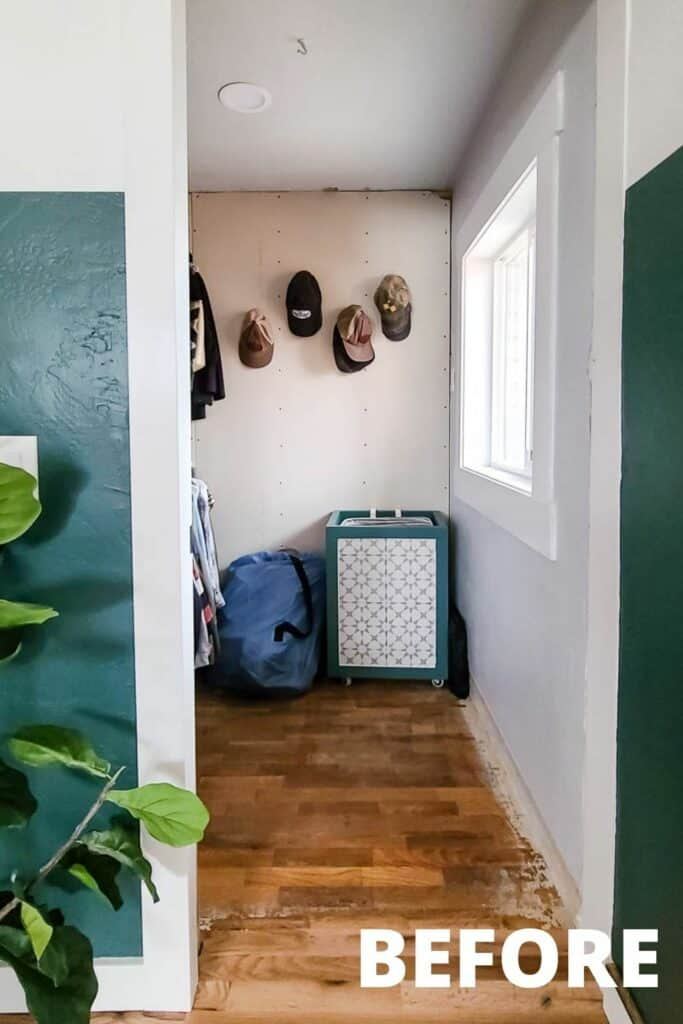 small walk in closet with hats hanging and laundry hamper before renovating