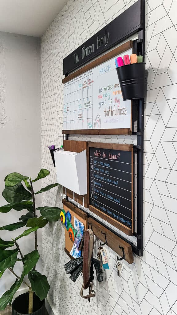 Customizable command center hanging on the white and black wallpapered wall beside the fiddle leaf fig tree in a black pot