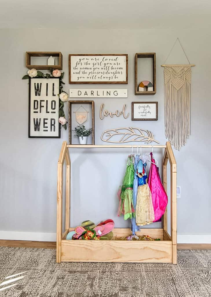 DIY wooden dress up storage with costumes and accessories below the boho farmhouse gallery wall in little girl's room
