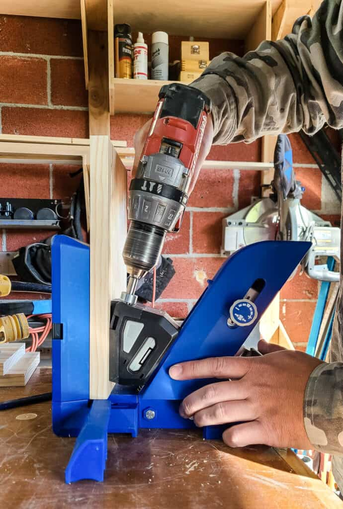 Side view of man drilling a pocket hole in a piece of wood using a Kreg 720 Pro Pocket Hole System