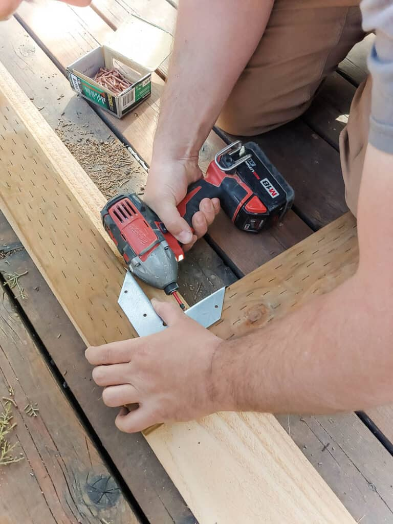 Man attaching two boards for frame on a gate and corner brackets with deck screws using drill