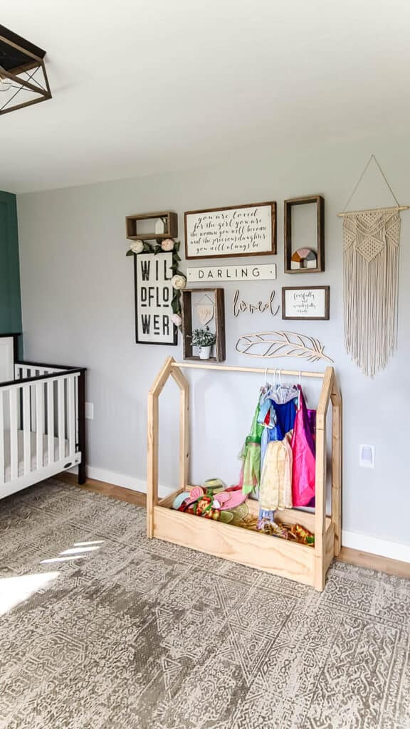 Full view of DIY wooden dress up storage with costumes and accessories below the boho farmhouse wall decor and beside the wooden white and black crib