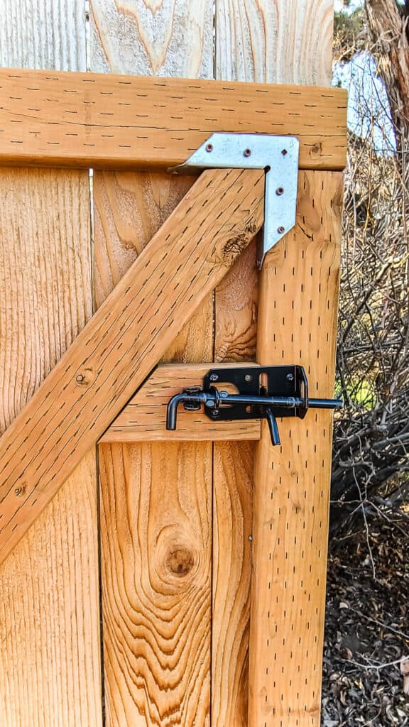 Wooden gate with wood brace and handle and latch attached.
