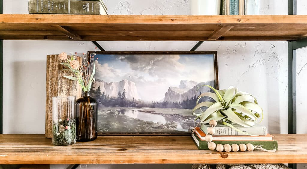 shows a shelf with glassware and vintage books with a mountain painting behind it