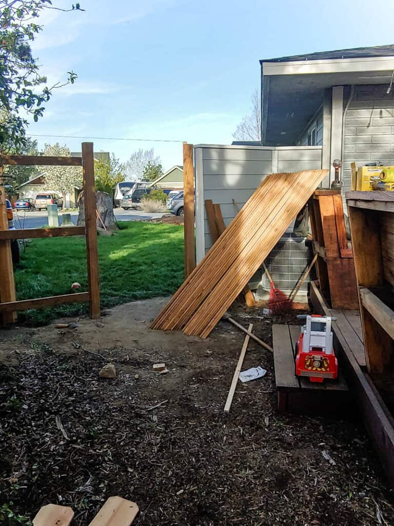 Scrap woods, toy truck and unused home items at the wooden fence before a gate is built.