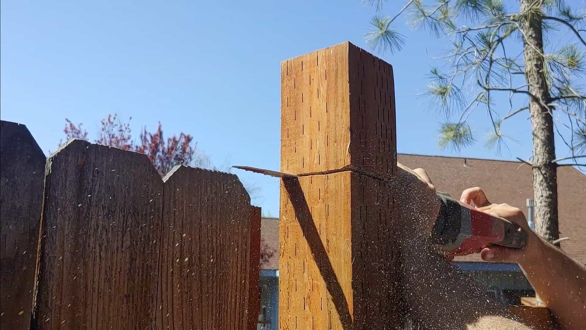 shows a reciprocating saw cutting the top of a fence post