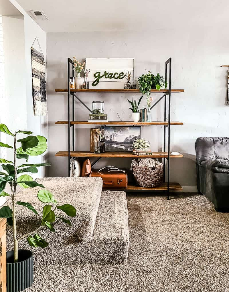 shows a shelf case with a white wood sign with the word grace made out of moss on it and other clear vases and vintage books