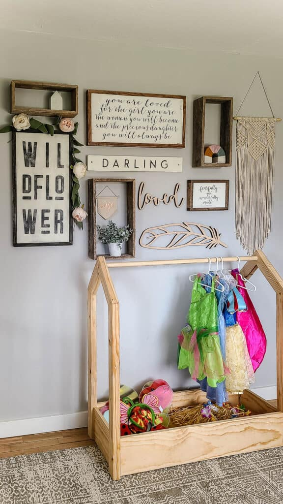 Boho gallery wall with wood signs and reclaimed wood shelving with macrame in little girl toddler room with light wood DIY dress up storage with disney dress up clothes hanging on rack