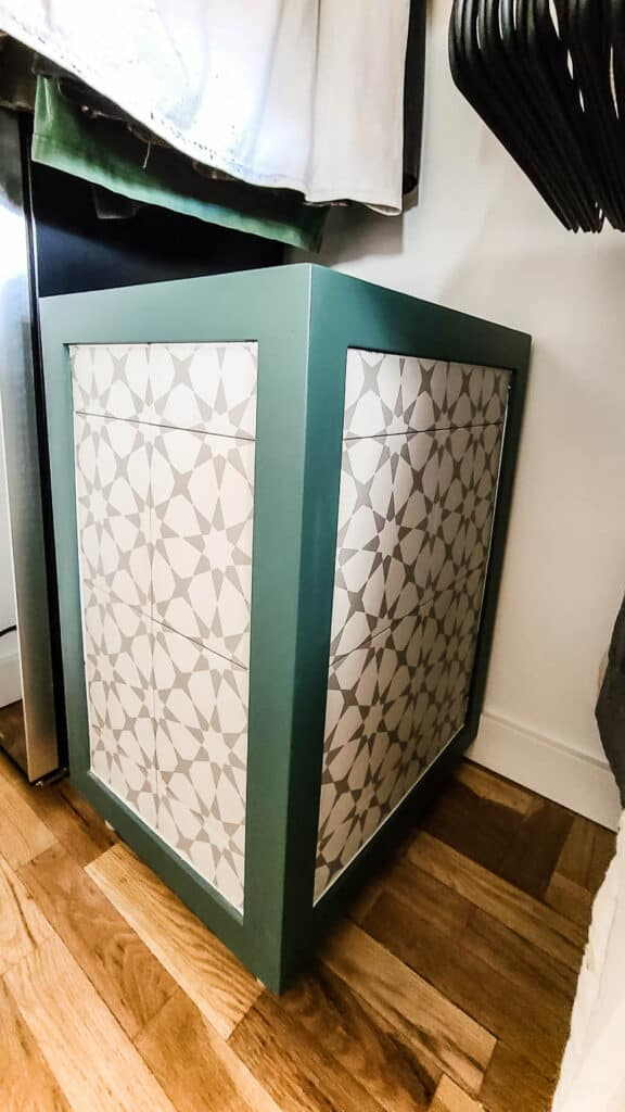 Wooden hamper with patterned tiled edges and green trim in the master closet