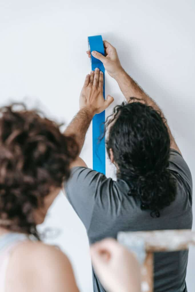 Woman behind the a man wearing gray shirt sticking blue painter's tape on the white wall