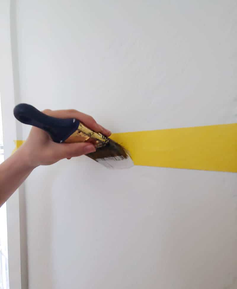 Hand of a woman holding a paintbrush covering the yellow painter's tape horizontally taped on the white wall to seal the tape edge and prevent bleeding or seeping under the tape