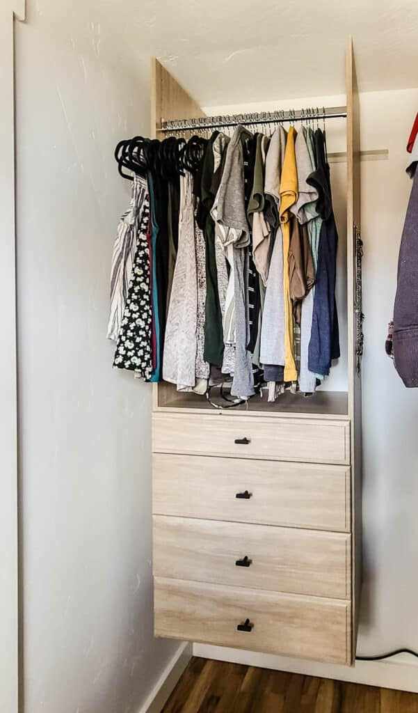 Clothes hanging above white closet