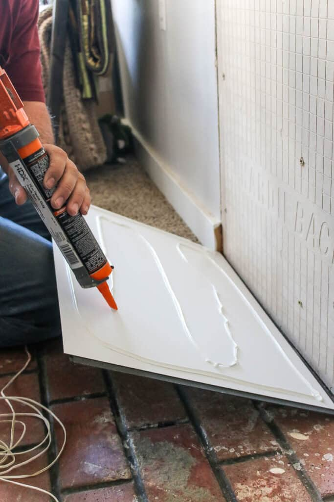 applying construction adhesive to the back of wall panels