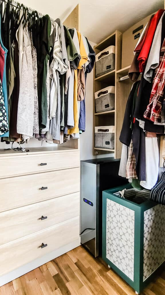 Hanging clothes and storage in the renovated master bedroom walk in closet with new light wood organization system