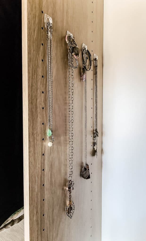 necklace organization in closet with 3M Command hooks on edge panel of closet system