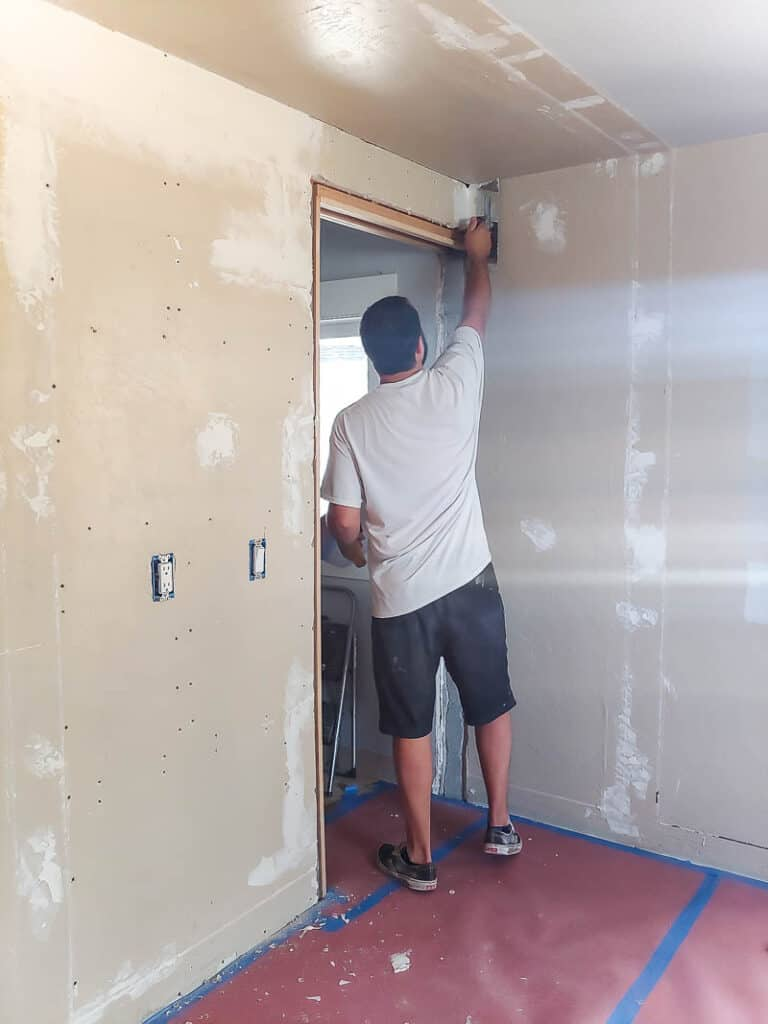 man applying trowel texture at the top of the wall and ceiling beside the walk in closet door