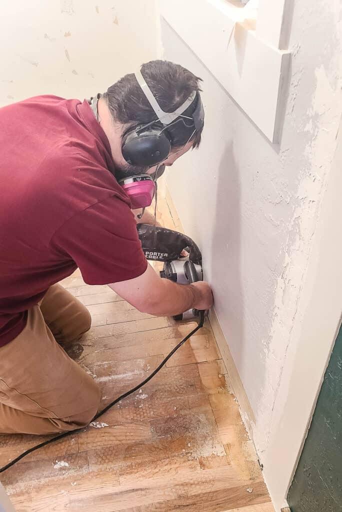 Man sanding hardwood floors with belt sander in closet