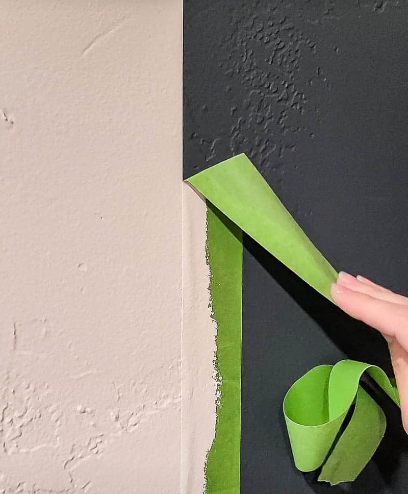 hand of a woman peeling off the green painter's tape with nice crisp paint edge from the wall between the white and gray painted wall