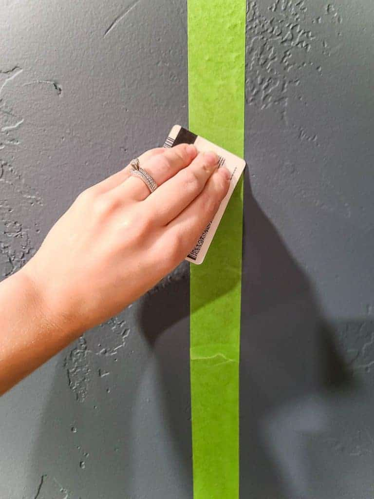 Hand of a woman with a ring holding a card swiping over the green painter's tape on the gray wall