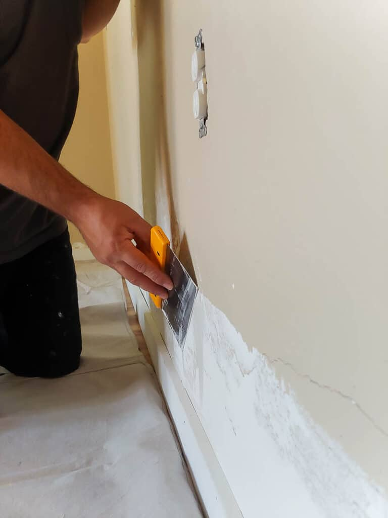 hand applying trowel texture at the bottom of the wall